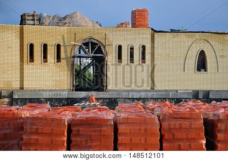 Grodno, Belarus - July 31, 2016: The construction of church of the beige brick with arched windows. Warehouse with red clay bricks in the foreground. Grodno, Belarus.