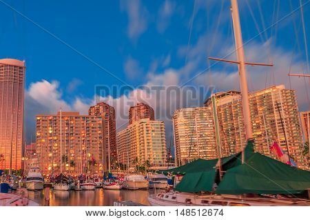Beautiful Honolulu skyline and boats docked at the Ala Wai Harbor the largest yacht harbor of Hawaii at twilight. On background, a luxurious hotel near Waikiki beach in Honolulu.