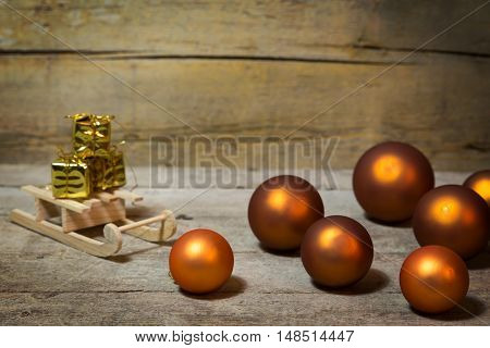 Orange Christmas Balls And Sledge With Gifts On Wood
