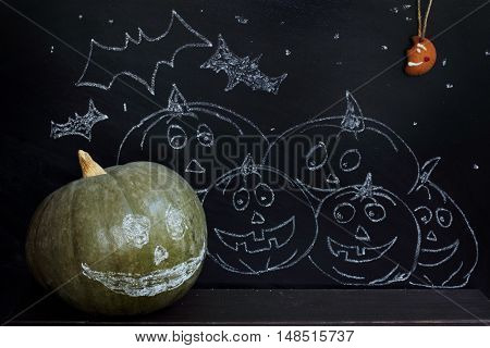 Green pumpkin with smile on the background of night marches painted pumpkins under the moon gingerbread / festive Halloween night