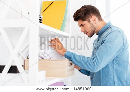 Handsome young casual businessman looking for documents from shelf in office