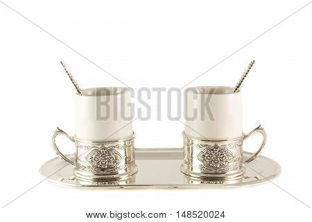 Two white porcelain coffee Cup with silver spoon on a tray on a white background