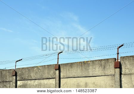 Concrete old prison fence with barbed wire on a background of blue sky.