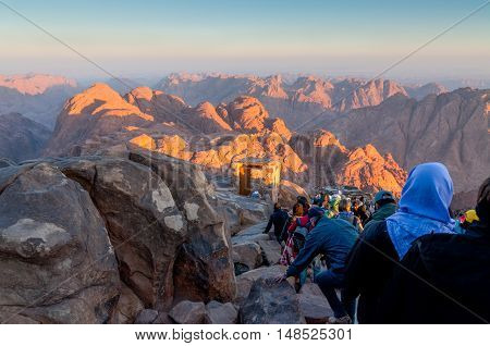 Mount Sinai Egypt - November 25 2010: Pilgrims and tourists on the pathway from the Mount Sinai peak in early morning. There are two primary routes up and down the mountain; they are hiking on the Steps of Penitence route. The mountain associated with Mos