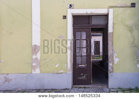 Facade of an old house with door from the street opened to a yard with next door. House number five. Mosonmagyarovar Hungary.