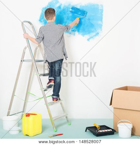 Teen boy makes repairs at home. Blue color painting wall with roller in hand. Child on ladder. Wall for text - copy space.