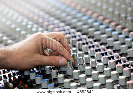 Hand on mixer in a recording studio, close up