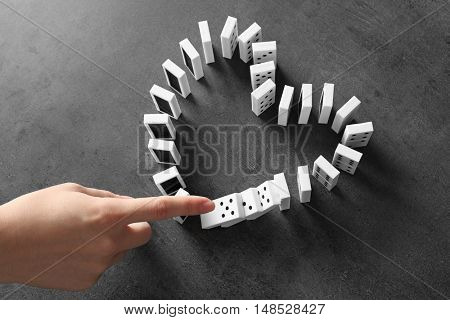Female hand pushing dominoes on grey background