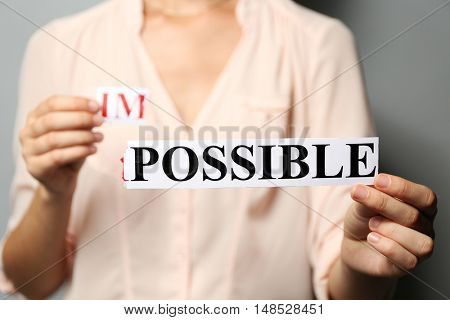 Woman holding word IMPOSSIBLE, close up