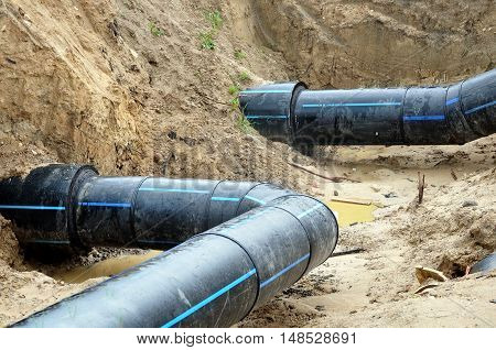 The process of laying of engineering and heating systems. Two black plastic bent pipes are in a trench of sand.