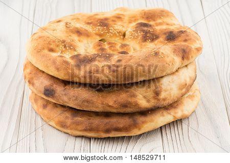 Uzbek bread on old white wooden table. Selective focus.
