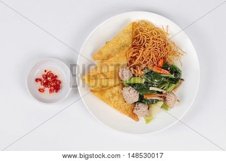 Crispy noodle topped kale soup with meatball and spicy sauce. Top view.