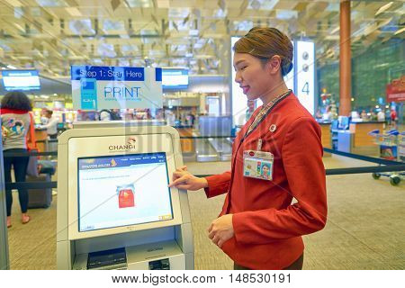 SINGAPORE - CIRCA AUGUST, 2016: indoor portrait of a woman near self check-in kiosk at Changi Aiport. Changi Airport is the primary civilian airport for Singapore.