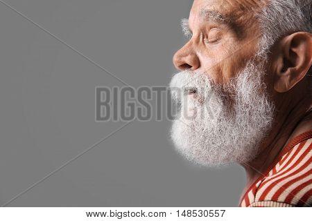 Elderly man in  stylish cloth on grey background