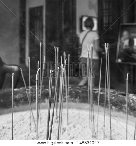 Black and white photo of incense sticks burning at the entrance to a Buddhist temple