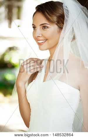 Young beautiful blonde bride in wedding dress and veil smiling, standing in park. Copy space.
