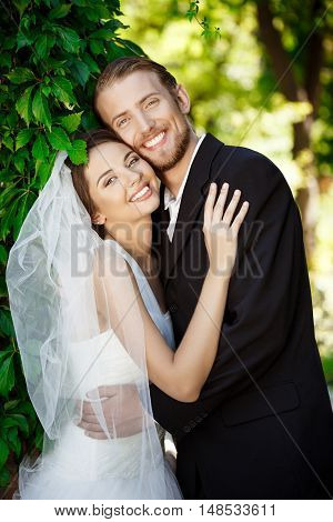 Happy newlyweds smiling, embracing, posing in park. Copy space