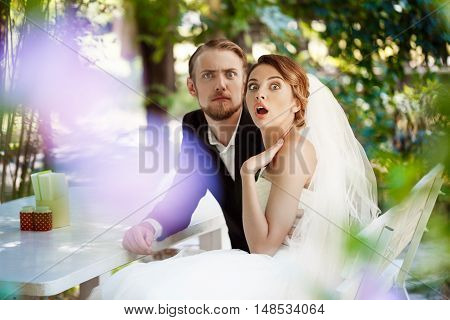 Young beautiful newlyweds fooling, sitting in cafe outdoors. Copy space.