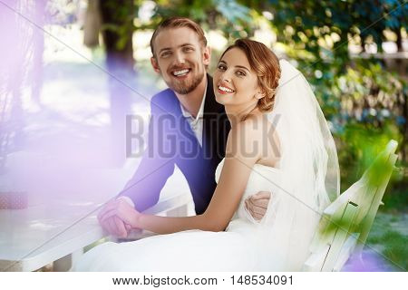 Young beautiful newlyweds smiling, embracing, sitting in cafe outdoors. Copy space.