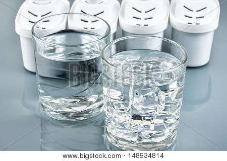 Glass of clean drinking water and water filters