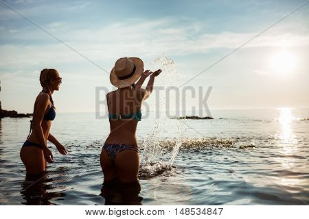 Young attractive girls rejoicing, swimming in sea. Copy space.