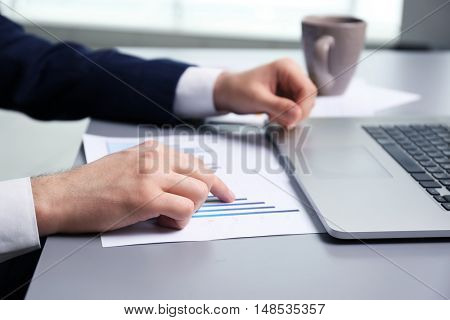Businessman working with schedule and laptop in office