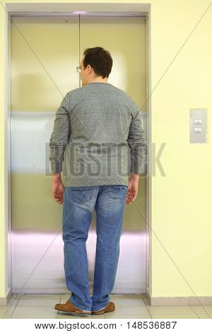 A man waiting for the elevator to come, view from the back