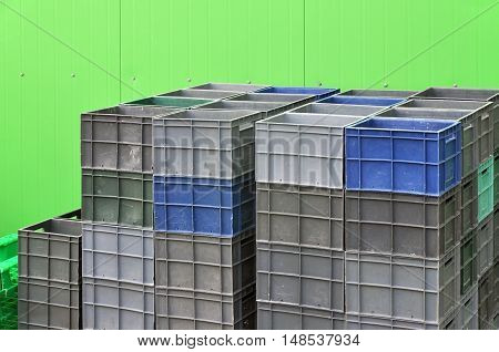 Plastic containers for storage and transportation of products on the background of green wall of the metal panels.