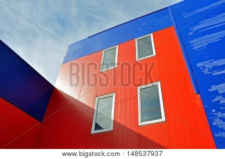 Grodno, Belarus - September 7, 2016: Industrial building of red and blue sandwich panels with windows lit by the sun. Look up. Grodno, Belarus.