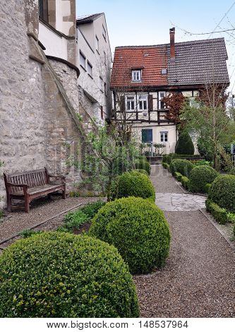 Waiblingen, Germany - April 16, 2016: Old courtyard of Waiblingen with leafy green bushes trimmed in the form of balls. Half-timbered house in perspective. Vertical view.