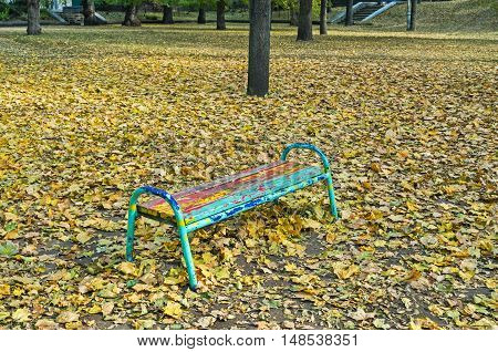 Multicolored bench in old park in the rays of evening sun
