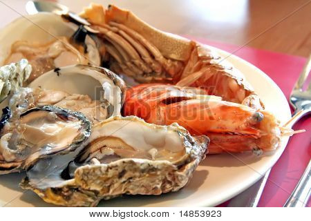 Assorted fresh seafood on a plate oyster clam shrimp scampi