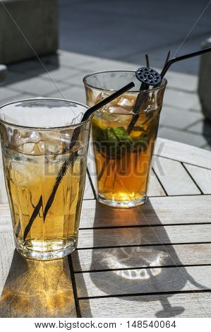 Glasses with cold tea and straws on the wooden table in the sunlight