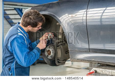 Young male car mechanic examining brake disc with caliper in garage