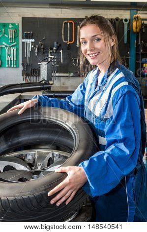 Portrait of smiling female mechanic mounting car tire on rim in garage