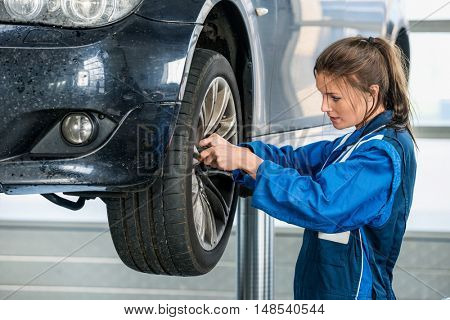 Side view of female mechanic changing tire from suspended car at auto shop