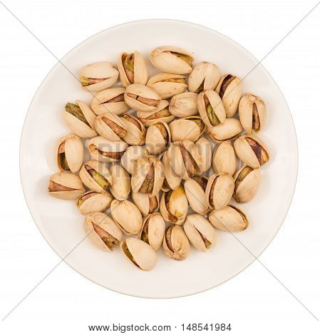 Roasted pistachio nuts in plate isolated on white background.