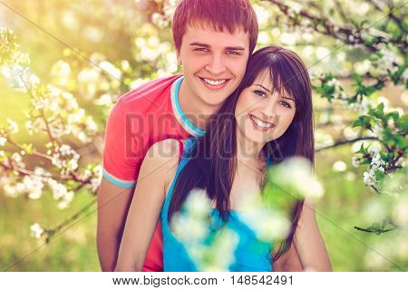Young couple in blooming garden hugging, toned image