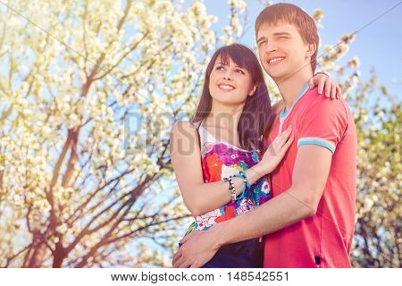 Young couple enjoying in blooming garden looking away