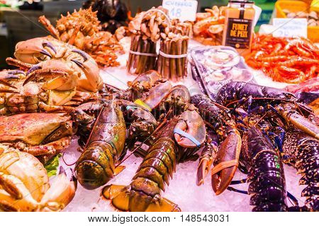 BARCELONA, SPAIN - AUGUST 25, 2016: Countertop with various fresh seafood in Boqueria market. Barcelona. Lobsters, shrimp, crabs and various shells beautifully laid out on the ice on the counter.