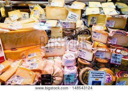 BARCELONA, SPAIN - AUGUST 25, 2016: Countertop with different cheeses with inscriptions at Boqueria Market. Barcelona. Cheese production in Spain