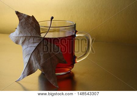 Artistic composition of sentimental autumn mood with tee and dry leaf.