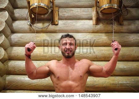 Happy muscular man overturns the two wooden buckets with water near log wall in a sauna