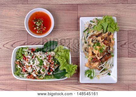 Fried oyster with herb and Spicy sour herb salad crab on brown.Top View