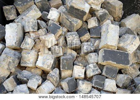 Pile of cobble stone bricks. Sooty bricks background
