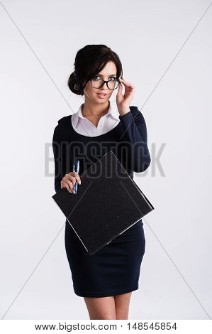 Closeup of an attractive young teacher holding a pen in the mouth, wearing nerd glasses and having a sexy attitude, isolated on white.