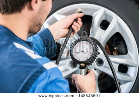 Rear view of mechanic checking tire pressure with gauge at garage