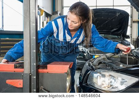 Young female mechanic in overalls Aligning the headlights of a car in garage