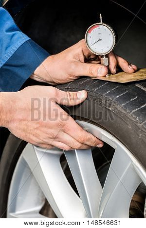 Closeup of male mechanic pressing gauge into tire tread to measure its depth at garage