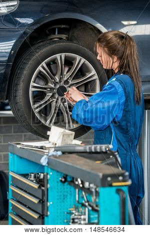 Young female mechanic changing wheel on car at garage